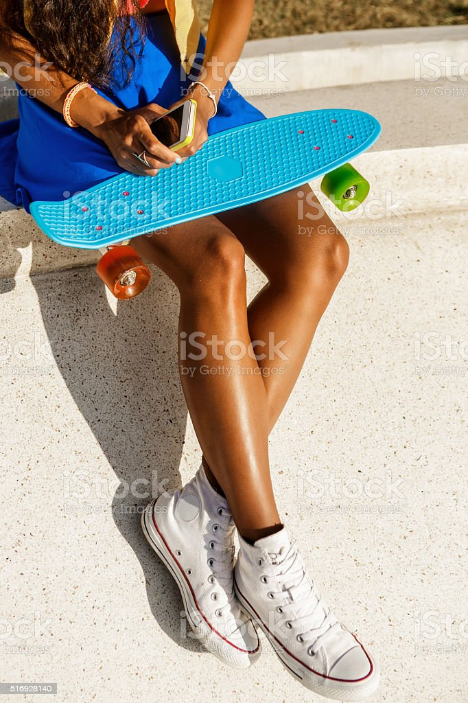 Beautiful black girl in blue skirt sit with her smartphone. stock photo