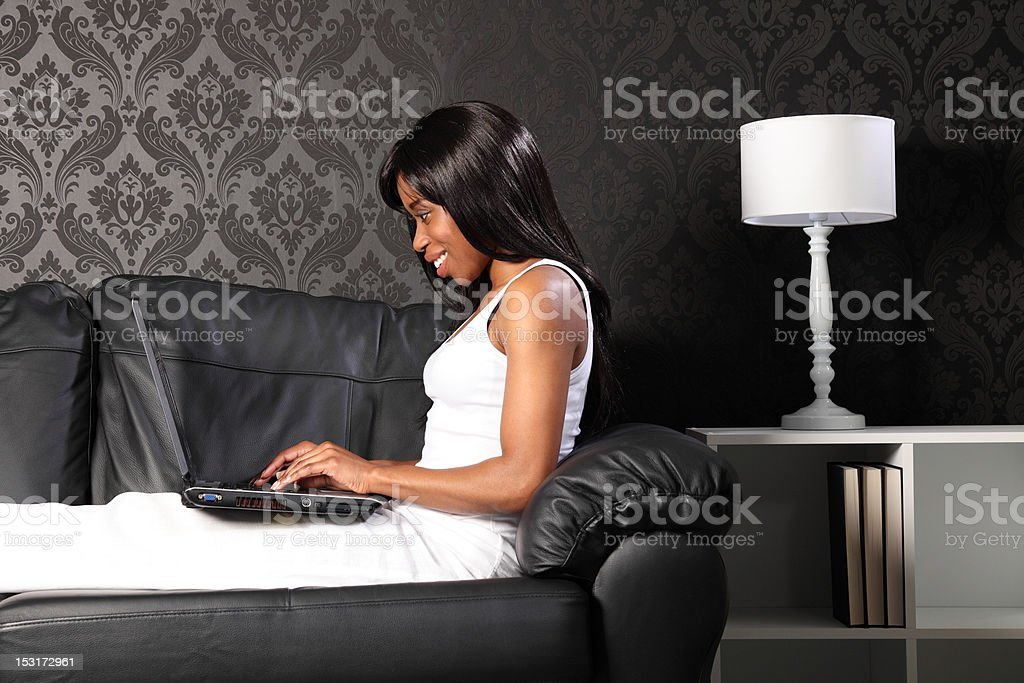 Beautiful black woman at home using laptop royalty-free stock photo