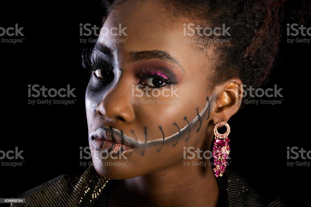 Beautiful black woman in sugarskull makeup, semi-profile. stock photo