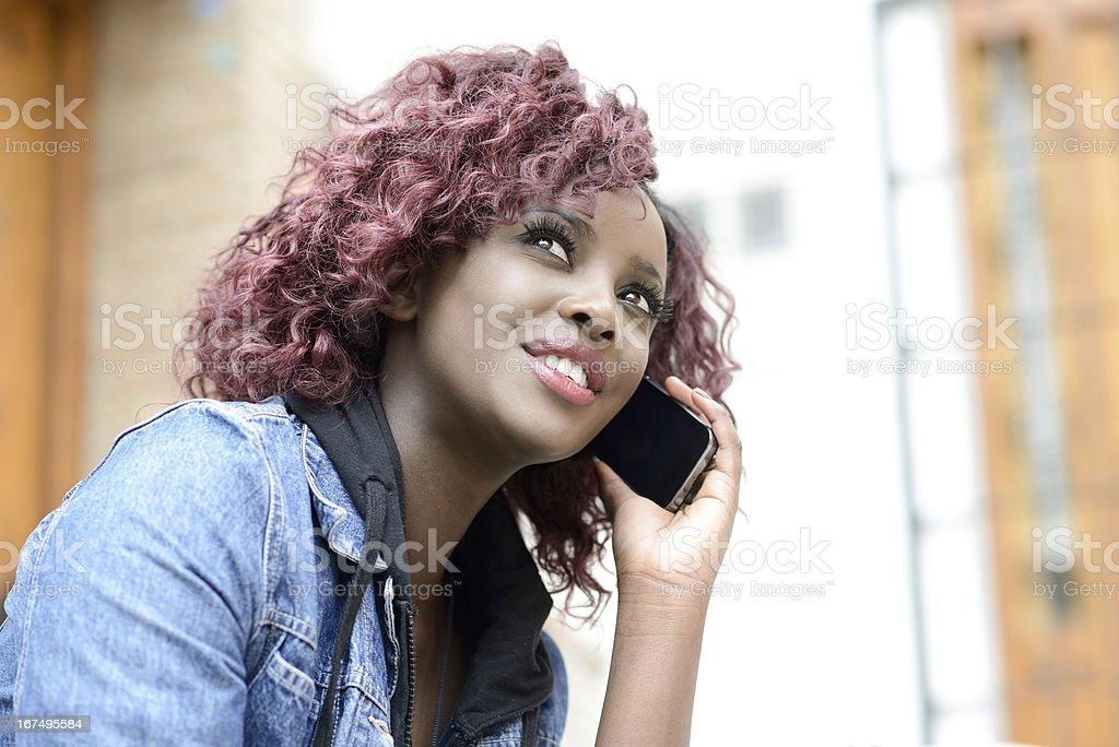 Beautiful black woman in urban background on the phone stock photo