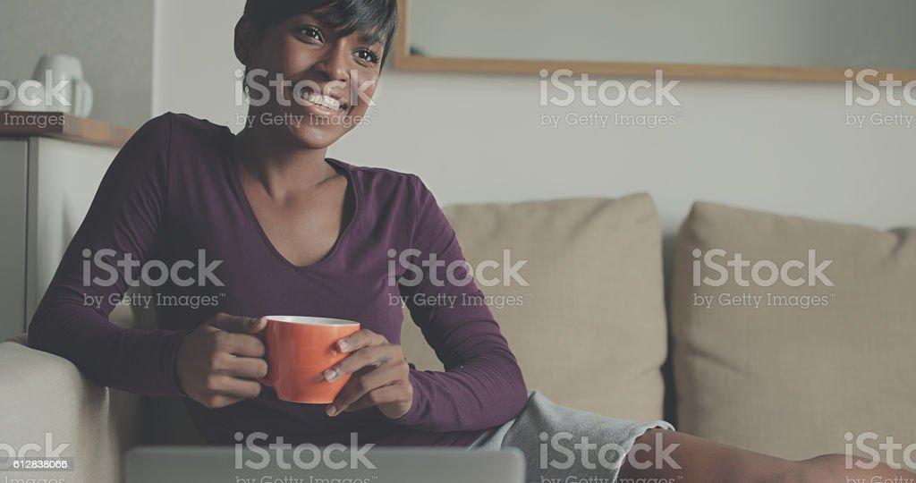 Beautiful black woman watching TV at home stock photo