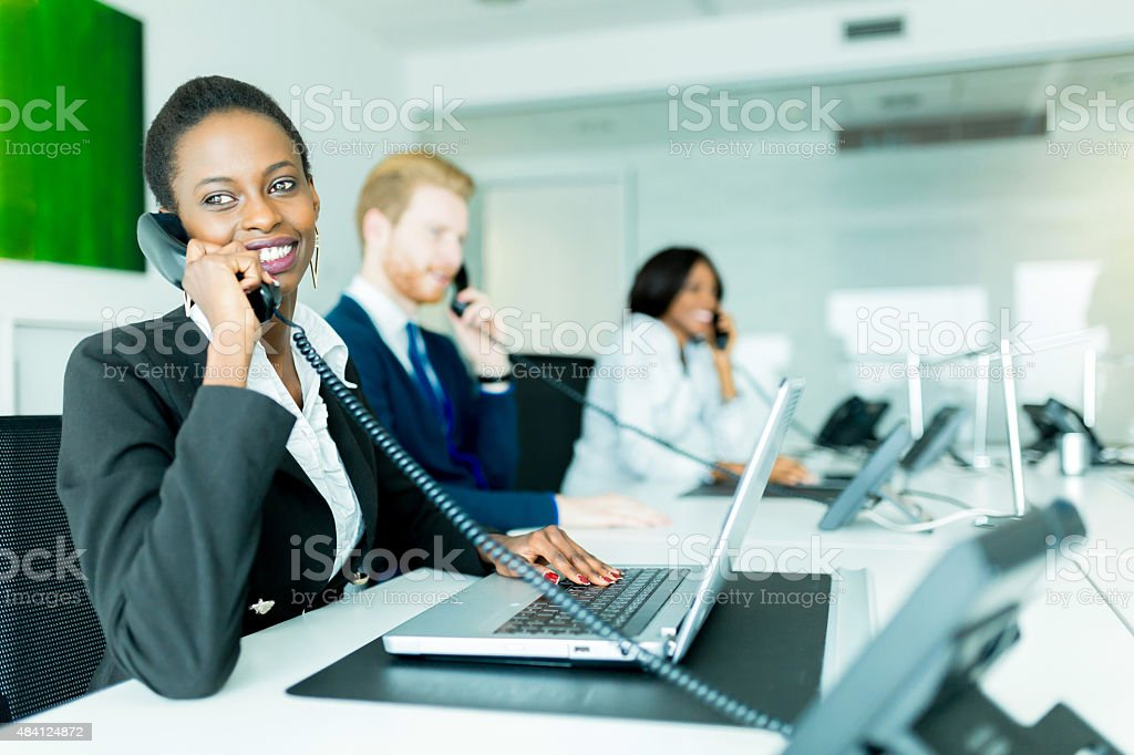 Beautiful, black, young woman working at a call center stock photo