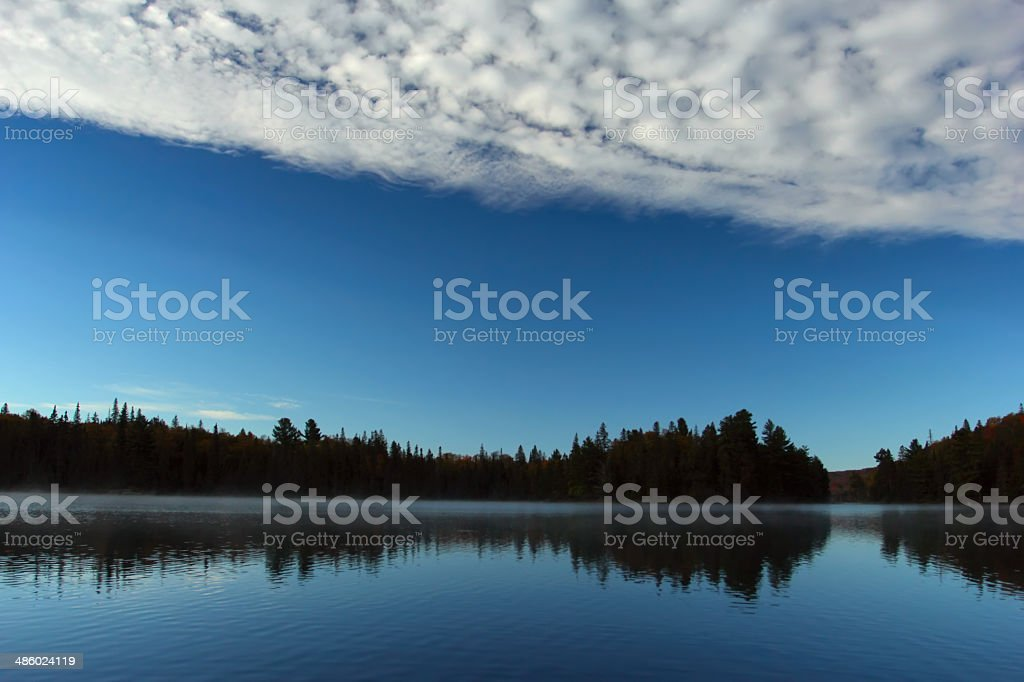 Beautiful ble lake and sky and white bank of clouds royalty-free stock photo