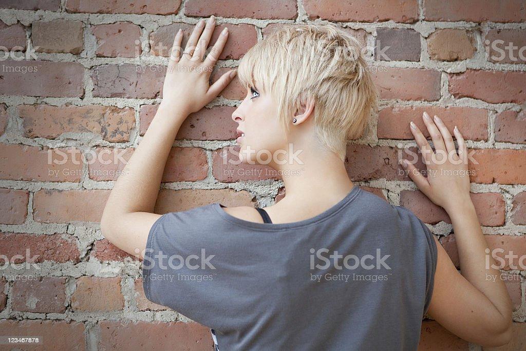 Beautiful blond against brick wall portrait stock photo