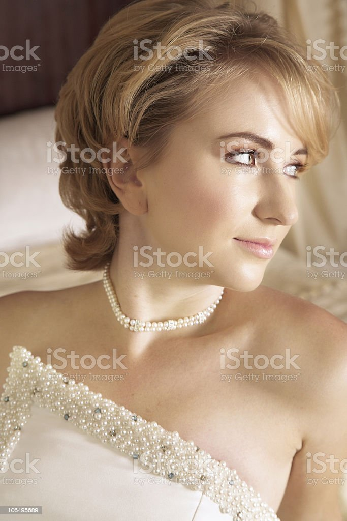 Beautiful blond bride in pearl white dress royalty-free stock photo