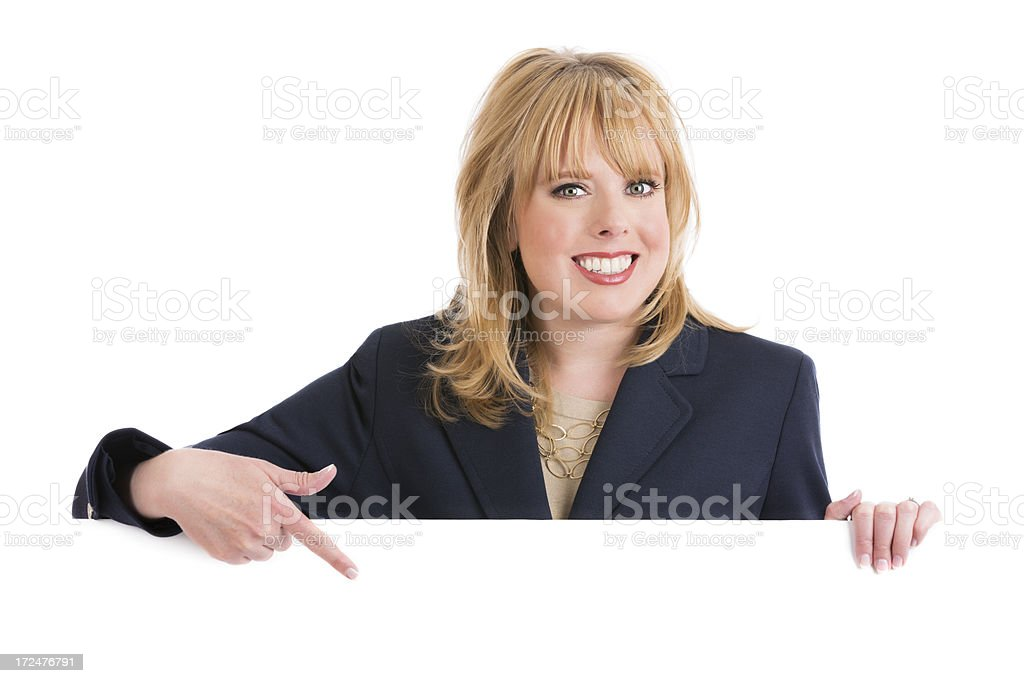 Beautiful blond businesswoman pointing to a blank sign royalty-free stock photo