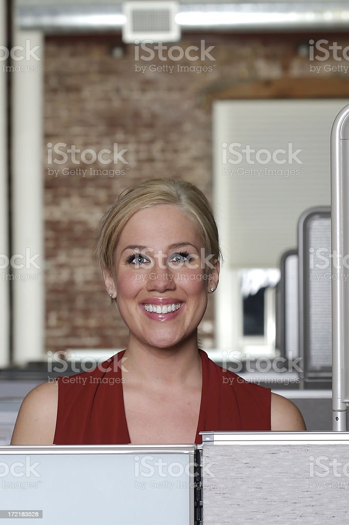 Beautiful smiling businesswoman at work looking over her cube. Copy...