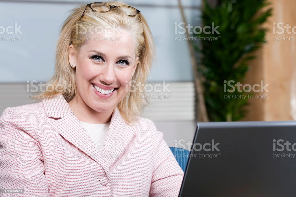 Beautiful Blond Businesswoman Using Laptop at Work, Smiling, Copy Space royalty-free stock photo