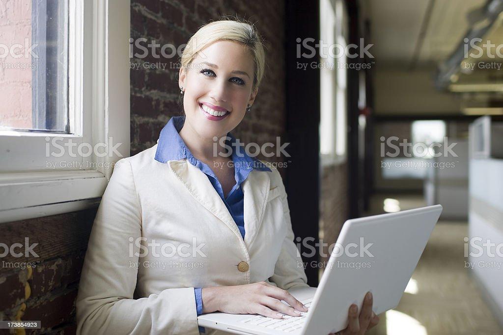Beautiful Blond Businesswoman Using Laptop in Office Hallway, Portrait, Copyspace royalty-free stock photo