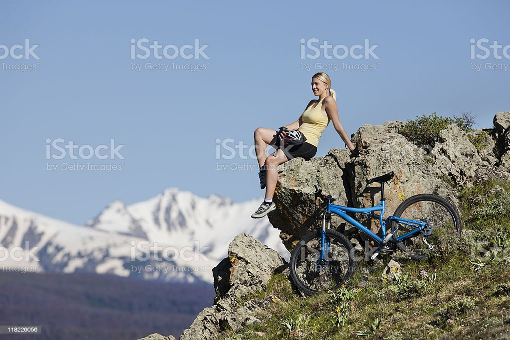 Beautiful Blond Female Sitting On Top Of Rock In Mountains stock photo
