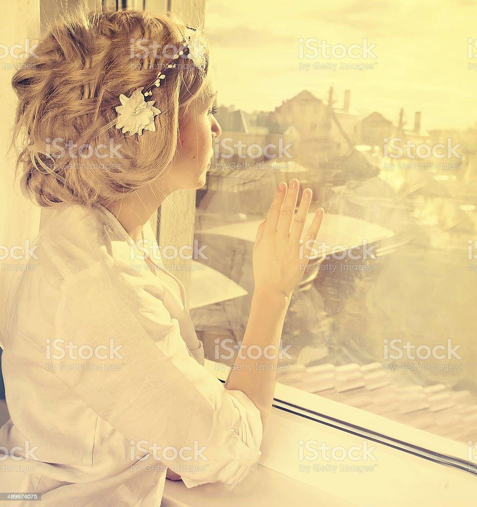 beautiful blond girl at window stock photo