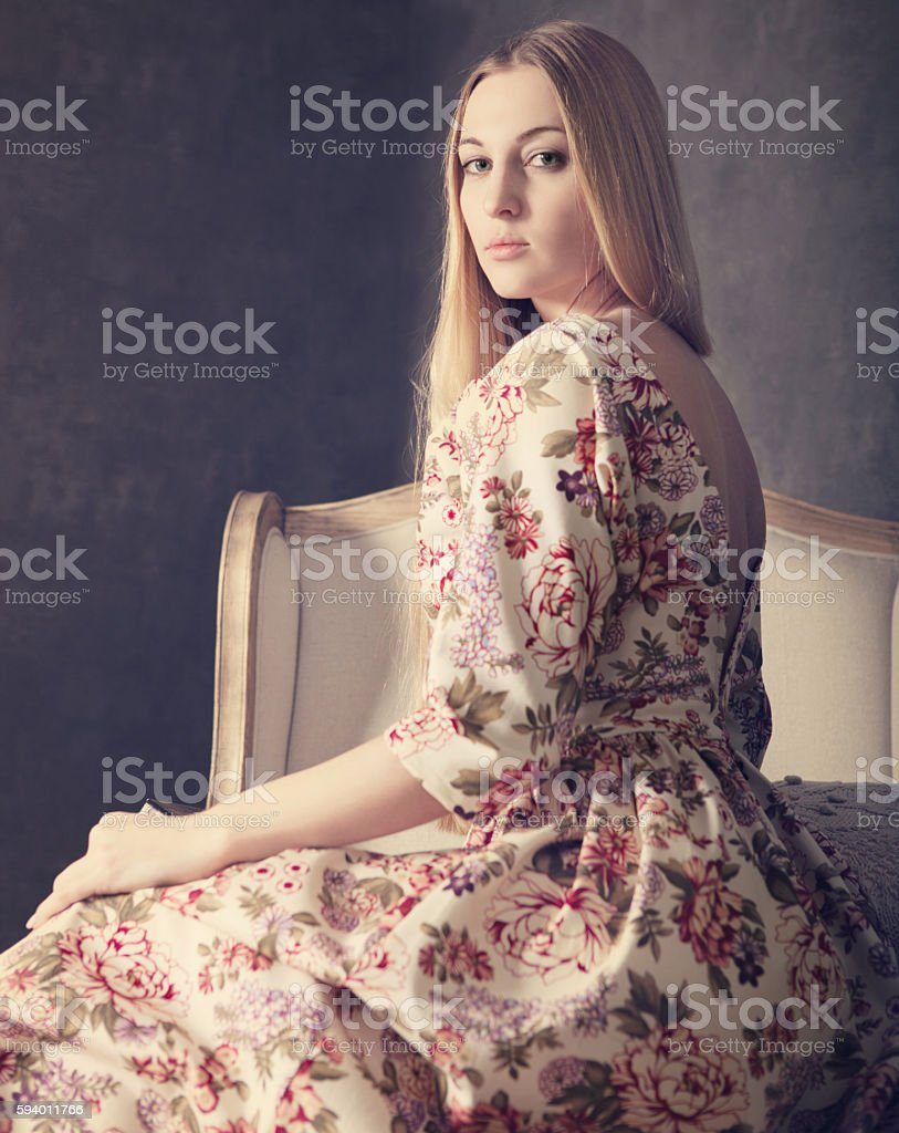 Beautiful blond girl in long dress at living room stock photo
