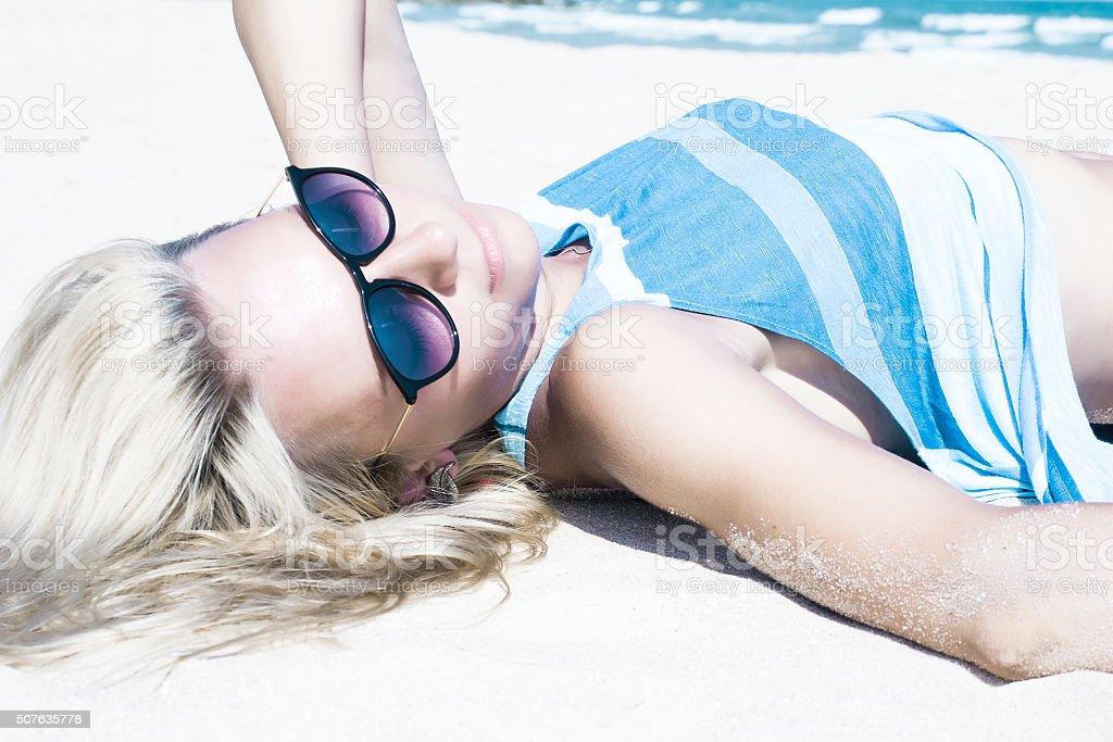 Beautiful Blond Girl lying On a Beach in Sunglasses stock photo