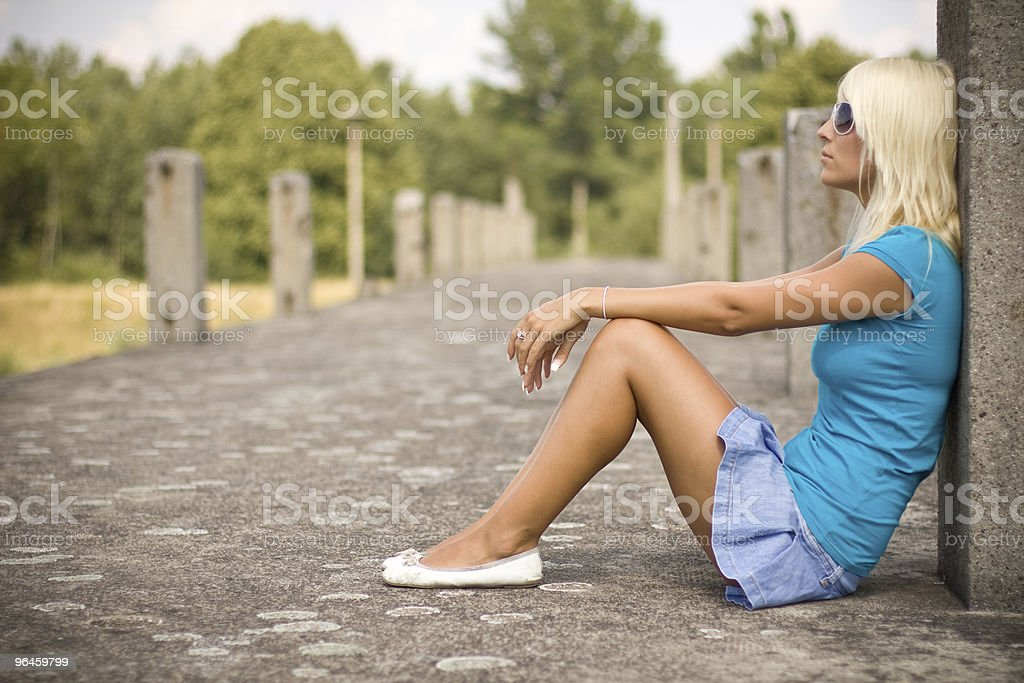 beautiful blond girl relaxing on the old bridge stock photo