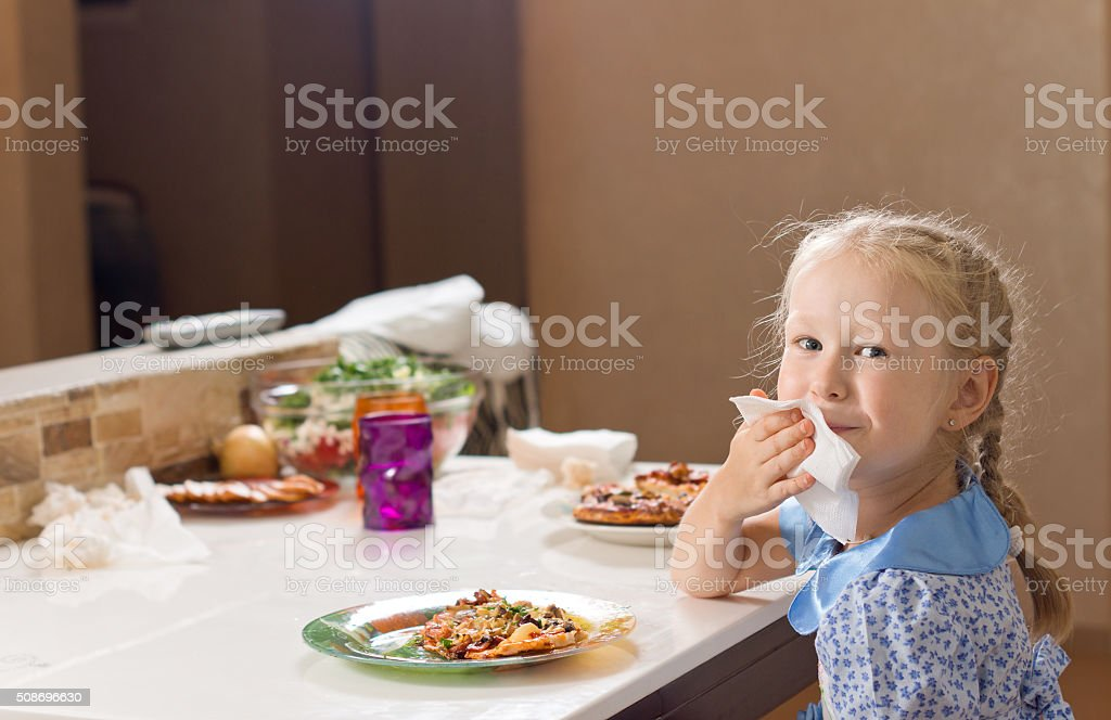 Beautiful blond girl wiping her mouth on a napkin stock photo