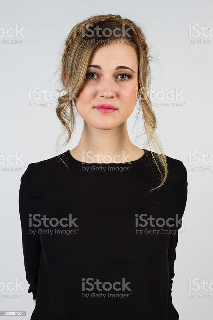 Beautiful blond girl with blue-green eyes on a white background. stock photo