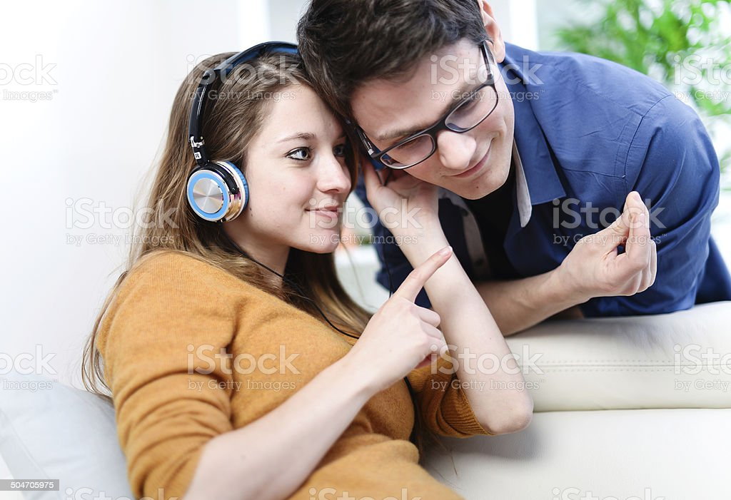 beautiful blond listening to music while her boyfriend watching royalty-free stock photo
