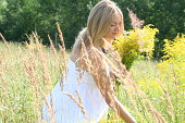 Beautiful blond pregnant woman in white dress picking flowers