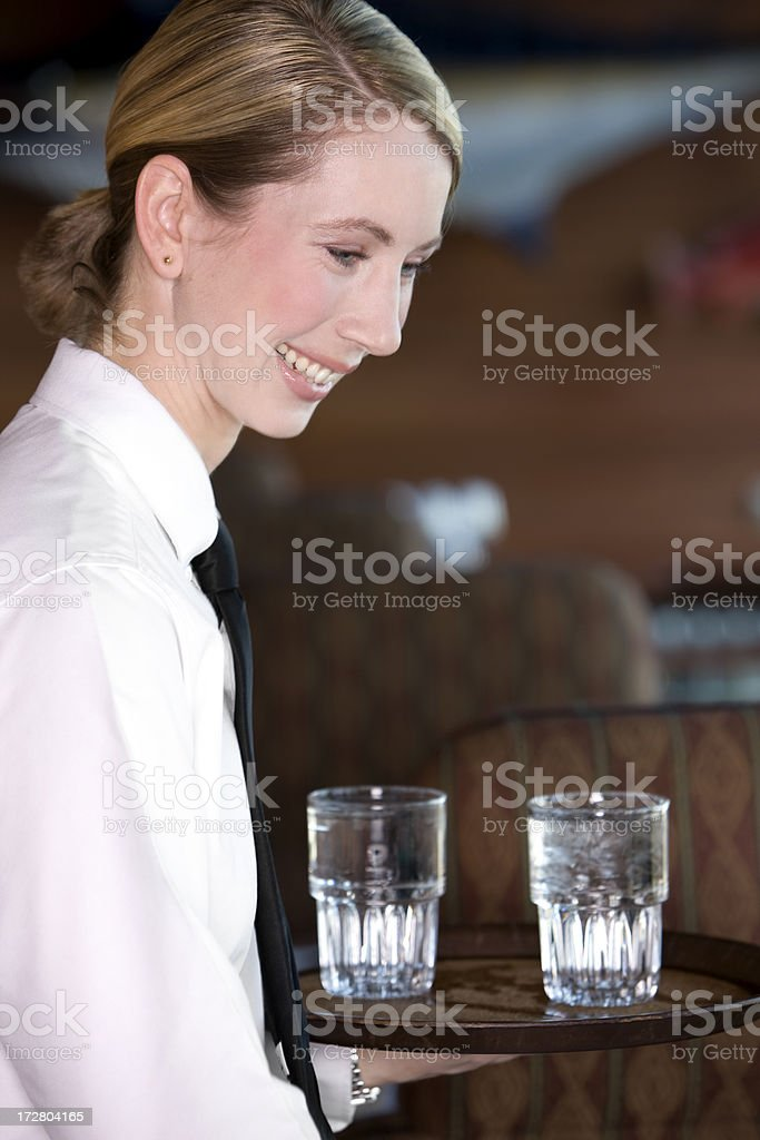 Beautiful Blond Restaurant Waitress Serving Water Glasses, Smiling royalty-free stock photo