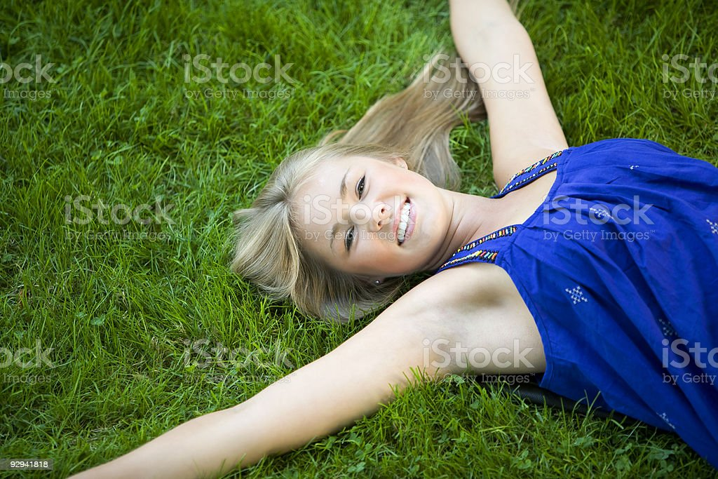Beautiful Blond Teenage Girl Lying on Green Grass royalty-free stock photo