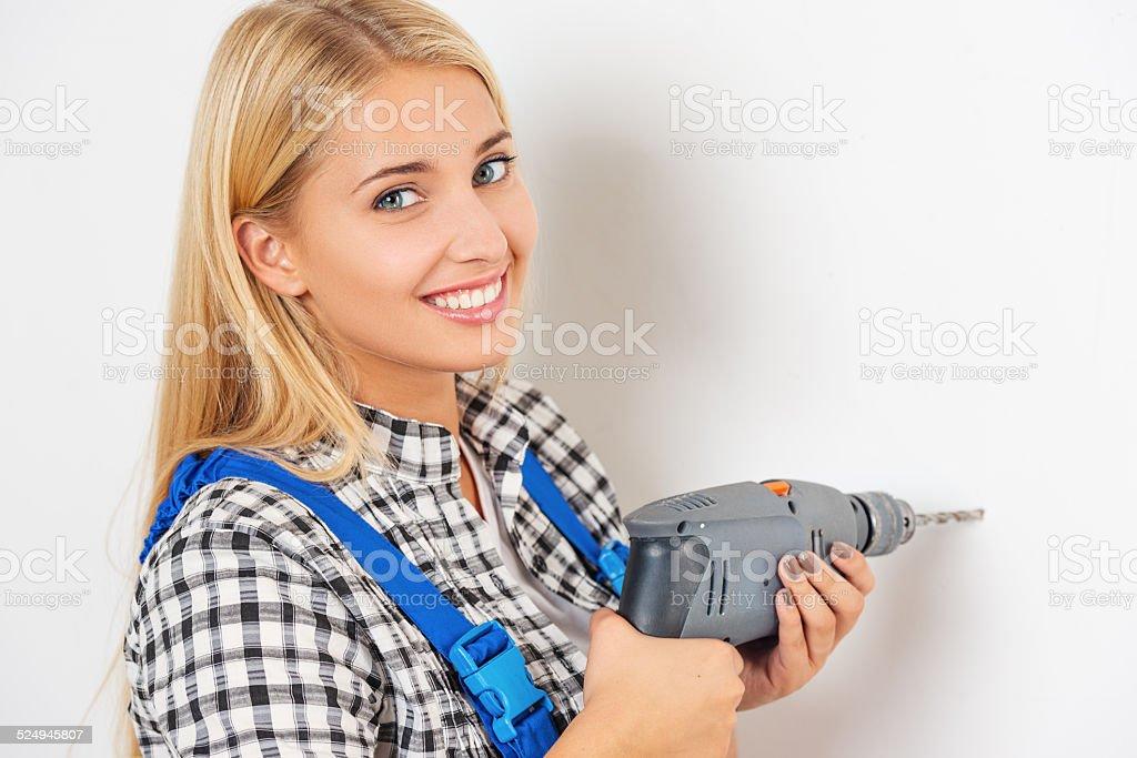 Beautiful blond using drill stock photo