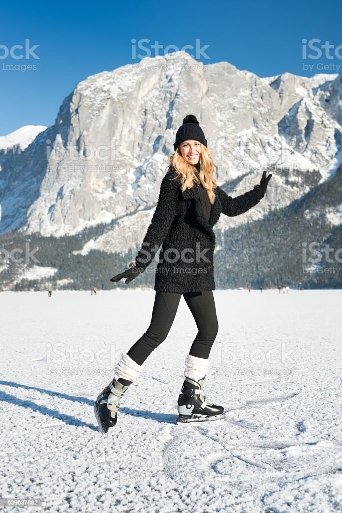 Beautiful Blond Woman Ice Skating, Frozen Lake Altaussee, Austria stock photo