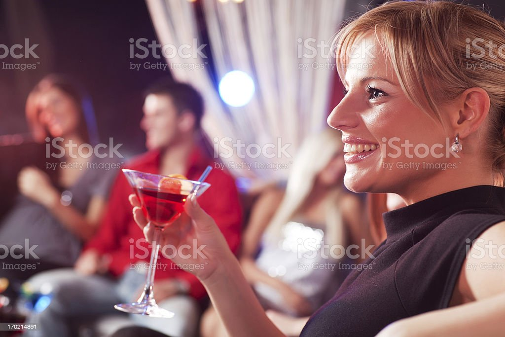 Beautiful blond woman in a bar holding a drink royalty-free stock photo