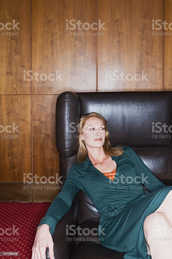 Beautiful blond woman in armchair stock photo