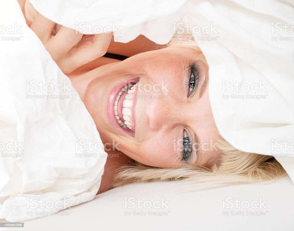 Beautiful Blond Woman in Bed Peeking through the Sheets (XXXL) royalty-free stock photo