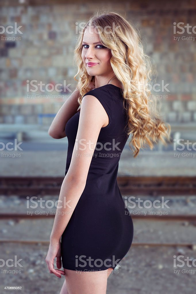 Beautiful blond woman in black dress stock photo