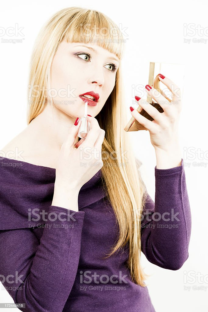 Beautiful blond woman is renewing her make up royalty-free stock photo