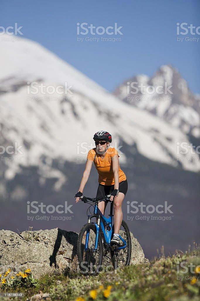 Beautiful Blond Woman Mountain Biking In Rocky Mountains stock photo