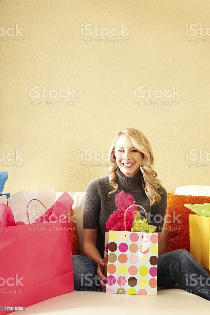 Beautiful blond woman on couch with shopping bags royalty-free stock photo
