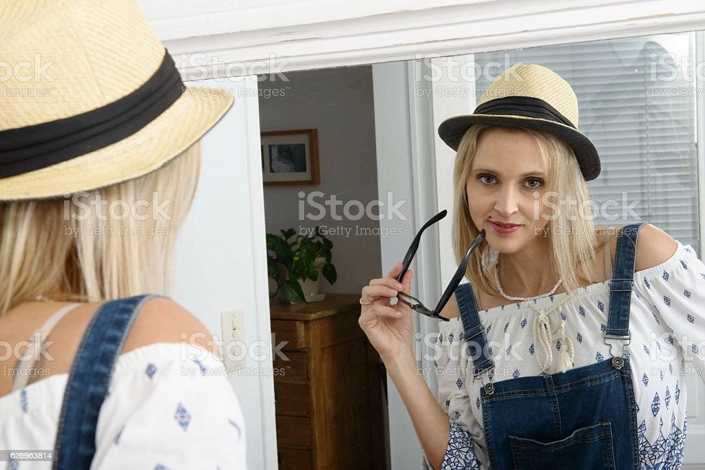 beautiful blond woman posing with summer hat in the mirror stock photo