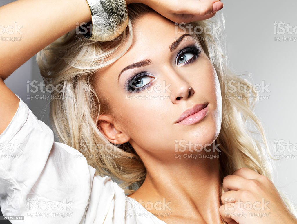Beautiful blond woman with long curly hair and style makeup stock photo