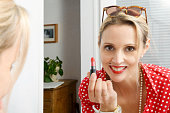 beautiful blond woman with mirror putting lip-gloss