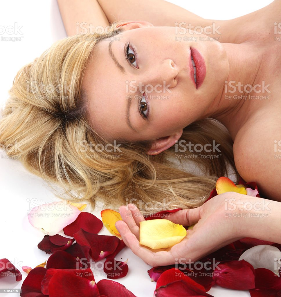 Beautiful blond woman with rose petals royalty-free stock photo