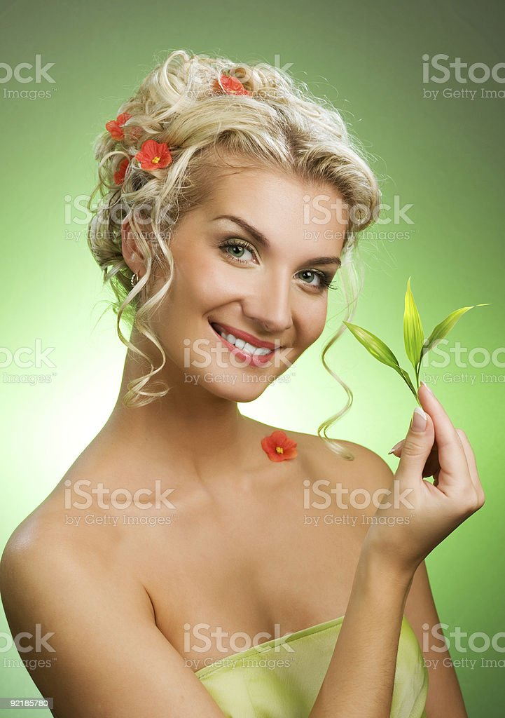 Beautiful blond woman with young plant. royalty-free stock photo
