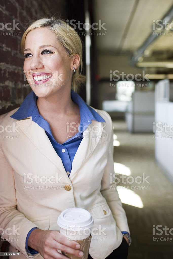 Beautiful Blond Young Businesswoman in Office with Coffee, Copy Space royalty-free stock photo