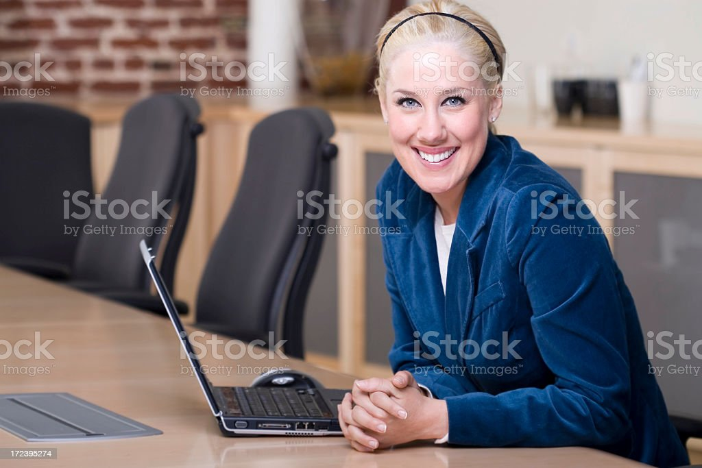 Beautiful Blond Young Businesswoman Using Laptop in Conference Room, Copyspace royalty-free stock photo