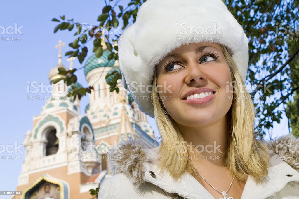 Beautiful Blond Young Russian Woman In Fur Hat By Church royalty-free stock photo