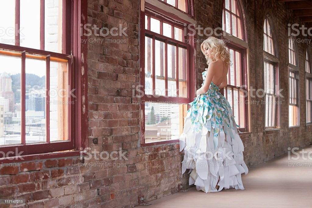 Beautiful Young Woman Fashion Model, Paper Gown, Standing at Windo stock photo