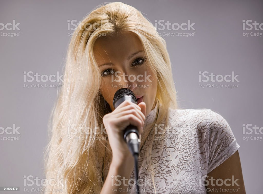 beautiful blond young woman singing into a microphone stock photo