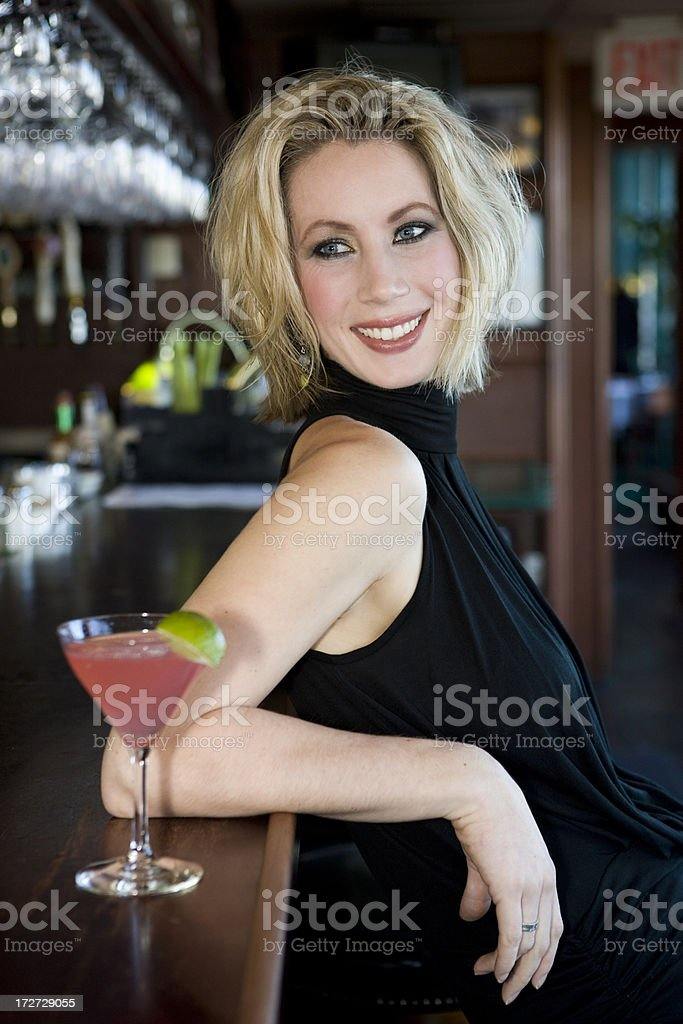 Beautiful Blond Young Woman Smiling in Bar with Cosmo Cocktail royalty-free stock photo