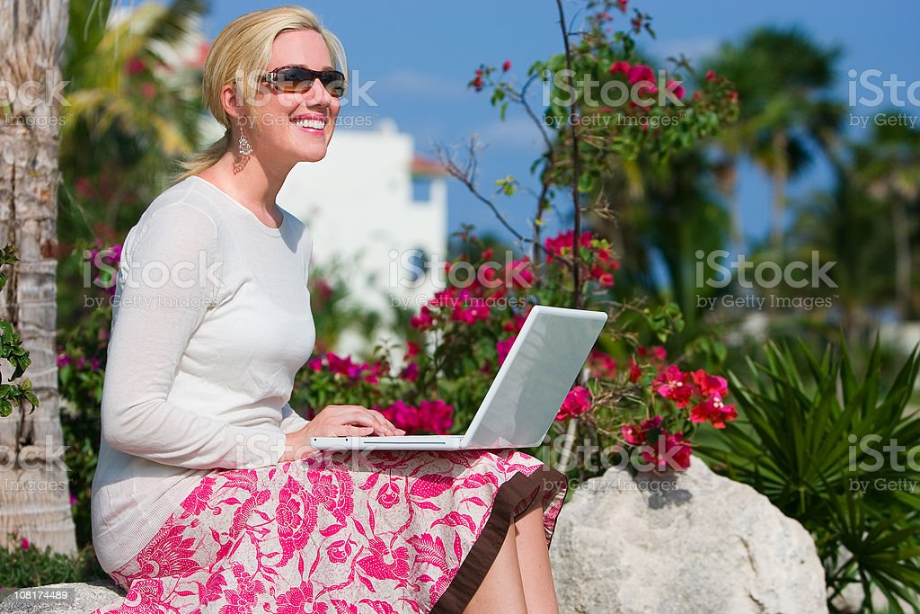 Beautiful Blond Young Woman Using Laptop Outdoors in Tropics, Copyspace royalty-free stock photo