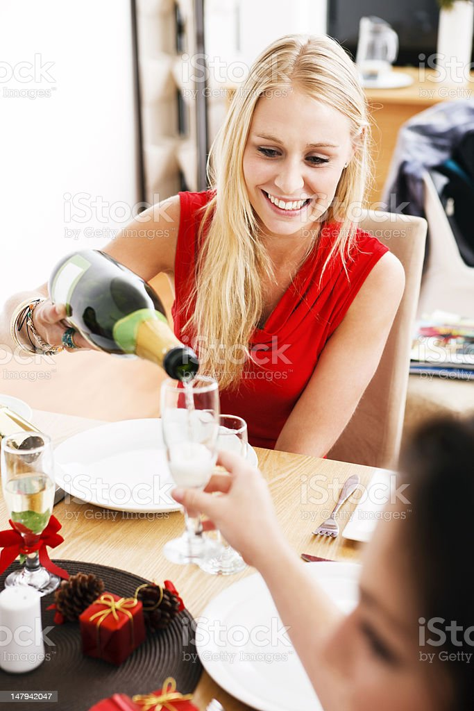 Beautiful blonde at decorated dinner table pours champagne royalty-free stock photo