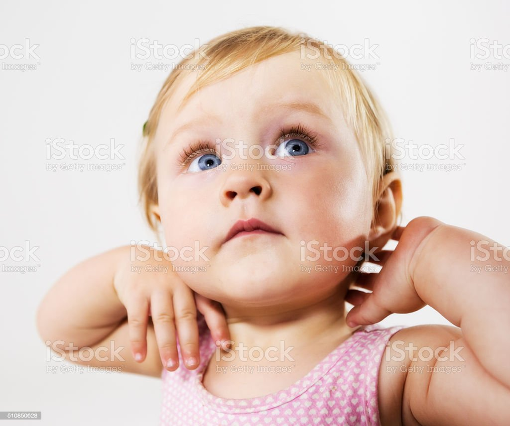 Beautiful blonde baby girl looks up, wide-eyed in fascination stock photo
