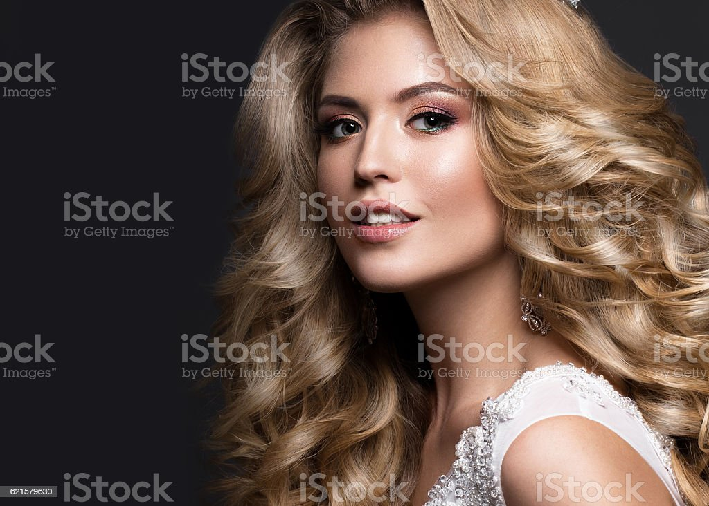 Beautiful blonde bride in wedding image with curls and crown stock photo