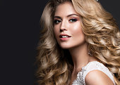 Beautiful blonde bride in wedding image with curls and crown