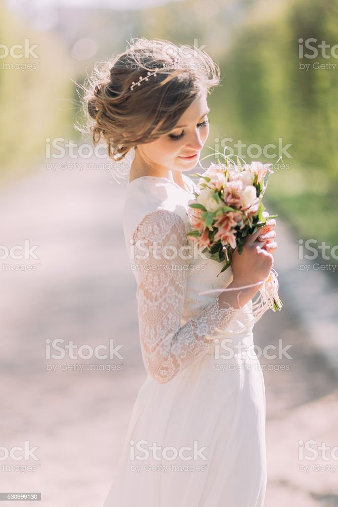Beautiful blonde bride with bouquet of spring flowers outdoor stock photo
